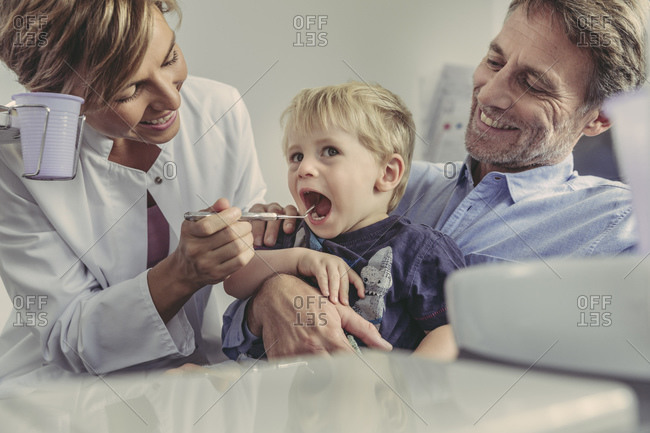 Female dentist examining little boy- sitting on his father's lap