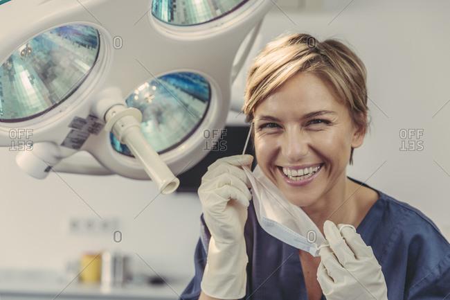Dental surgeon removing surgical mask- portrait