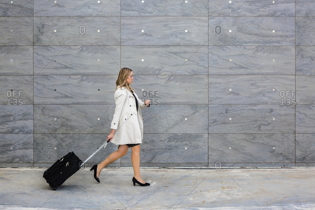 Businesswoman with suitcase wearing trench coat