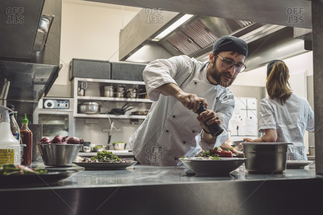 Low angle view of male chef seasoning food in commercial kitchen