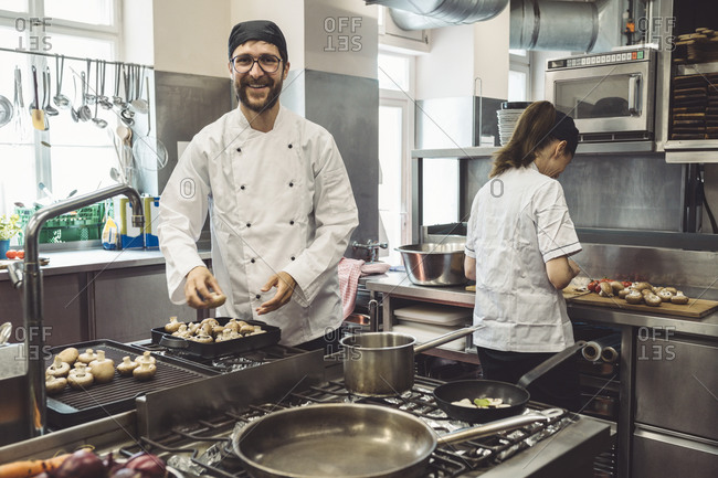 Portrait of smiling male chef cooking mushrooms in commercial kitchen