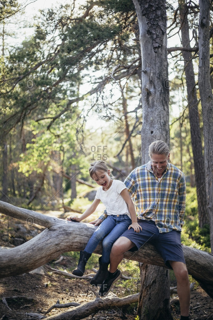 Happy father and daughter moving down on fallen tree in forest