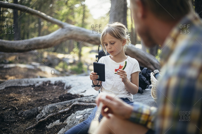 Daughter eating watermelon while using phone by father in forest