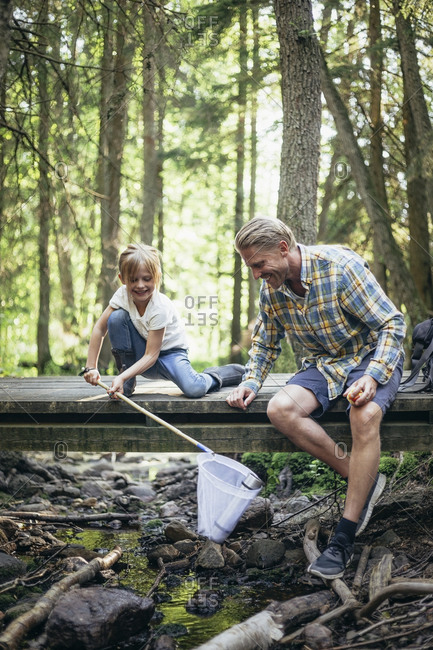 Smiling daughter holding bottle in fishing net by father in forest
