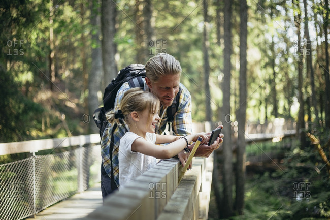 Smiling father with backpack and daughter looking at smart phone in forest
