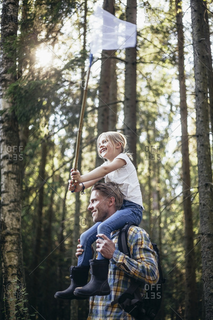 Low angle view of smiling father carrying daughter on shoulder with fishing net in forest