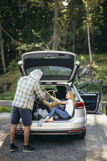 Side view of daughter covering father's face with fishing net while sitting in car trunk