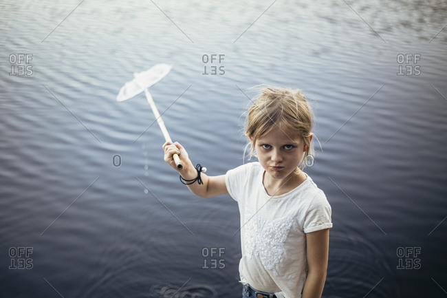 Portrait of girl with fishing net against lake