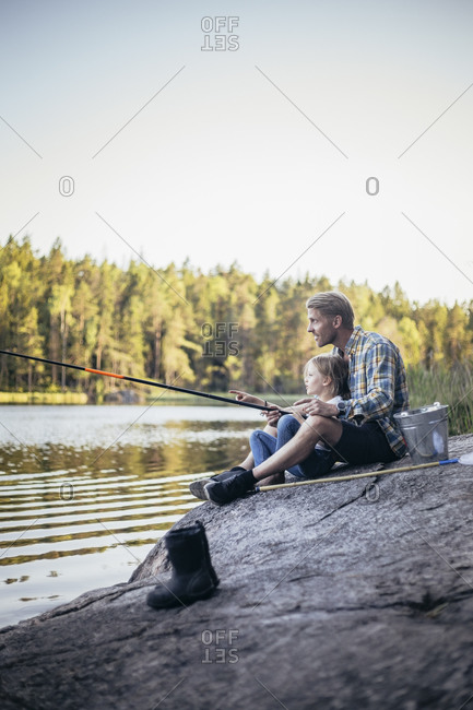 Father and daughter fishing at lake during weekend