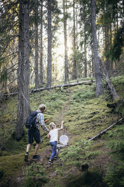 Low angle view of father and daughter with net walking in forest