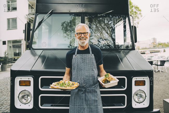 Portrait of smiling owner with food plate standing against commercial land vehicle