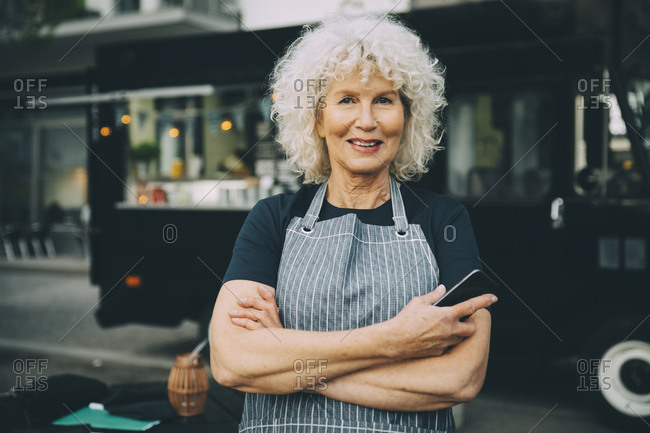 Portrait of senior owner with smart phone standing against food truck in city