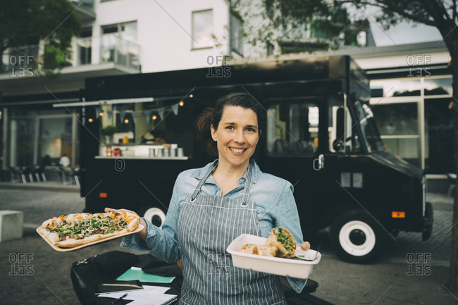 Portrait of smiling female owner with indian street food against commercial land vehicle