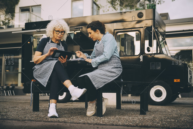 Senior female owner using digital tablet while sitting with partner against food truck