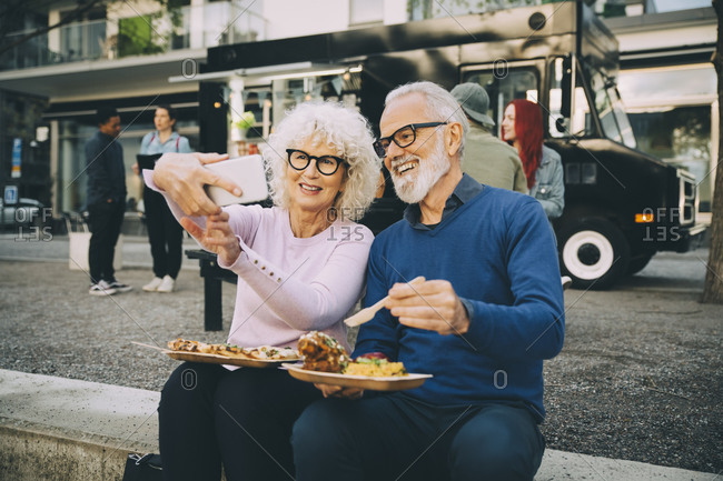 Smiling senior woman taking selfie with man eating meal against food truck in city
