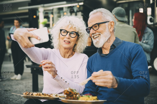 Senior woman taking selfie with smiling man eating meal against food truck in city