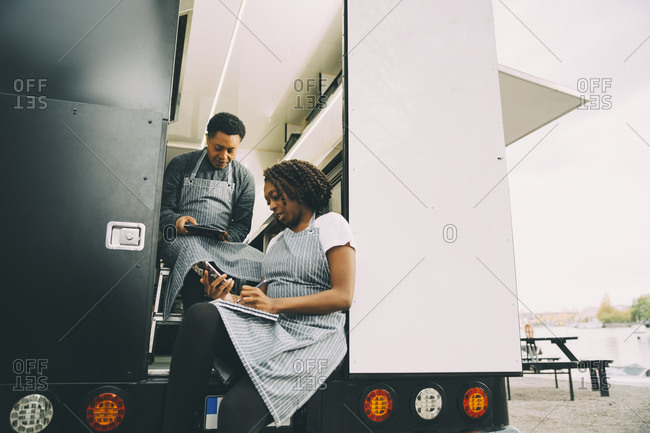 Female owner with assistant in food truck