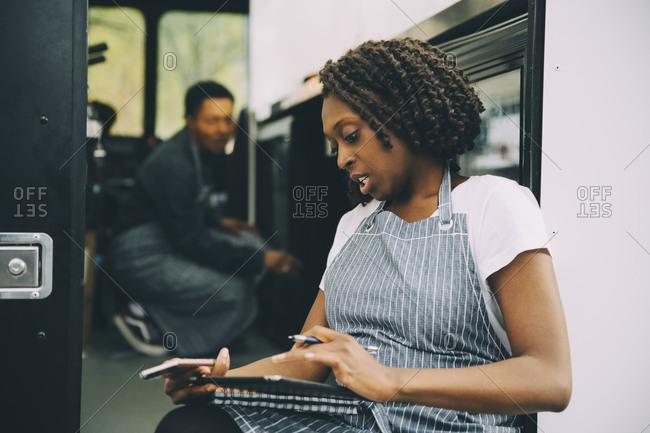 Female owner using digital tablet against food truck