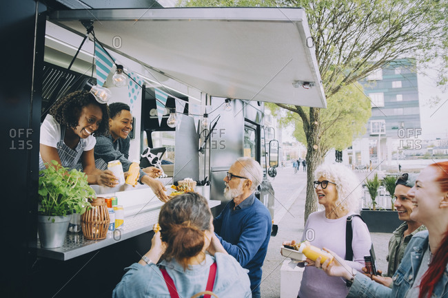 Smiling male and female customers talking to food truck owners in city