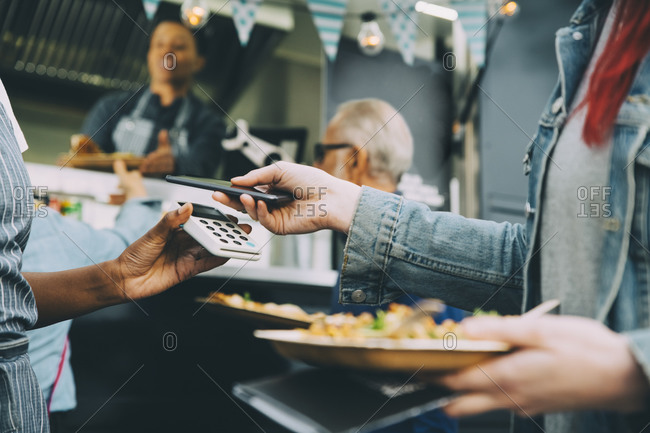 Midsection of customer paying through smart phone in city