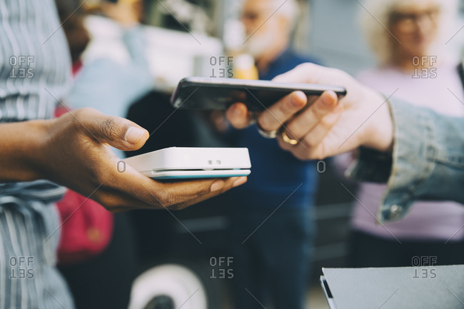 Cropped hand of customer paying through smart phone in city