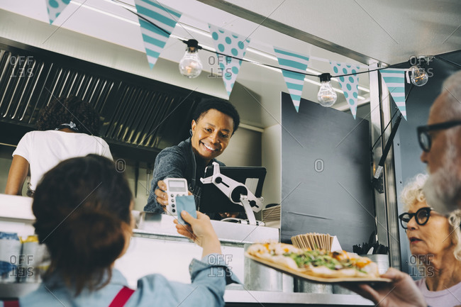 Smiling male owner talking to customer about contactless payment while standing in food truck