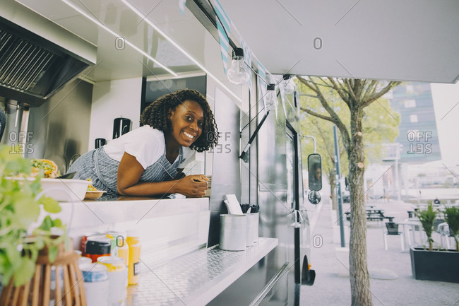 Portrait of smiling female owner standing in food truck