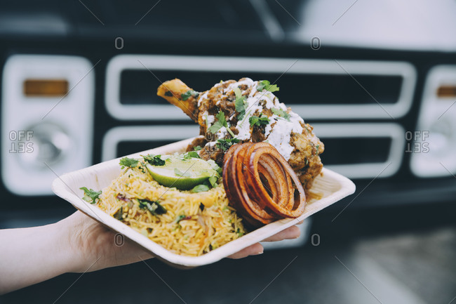 Cropped hand of female owner holding indian food plate in city