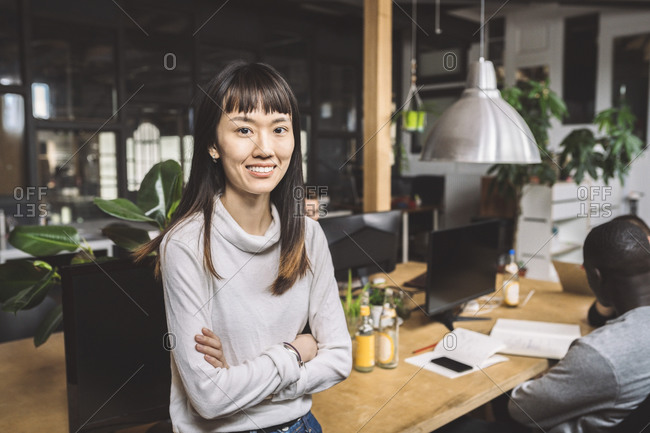 Portrait of smiling businesswoman with arms crossed at workplace