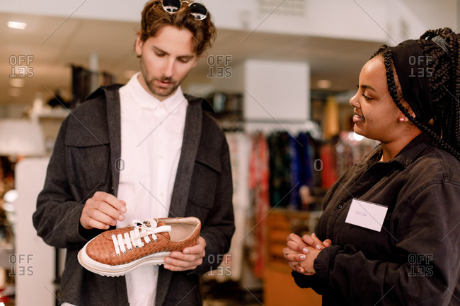 Smiling saleswoman showing shoe to male customer at retail store