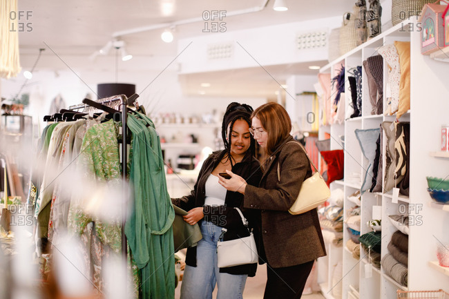 Side view of woman showing smart phone to friend in retail store