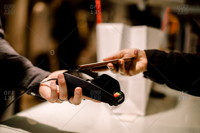 Cropped hand of female customer paying through phone at store