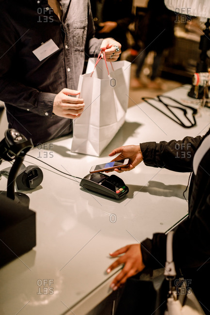 High angle view of female customer paying through smart phone at store