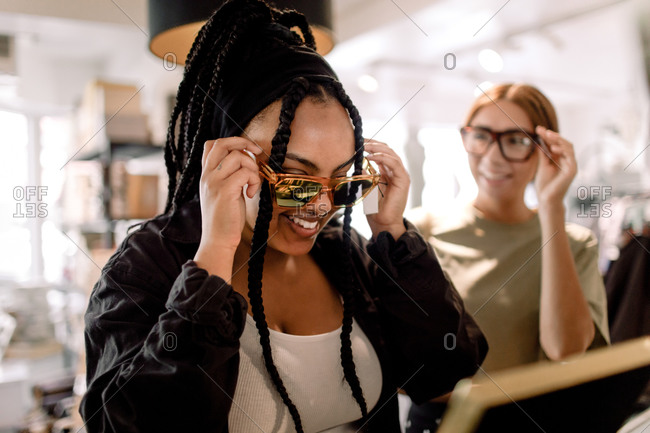 Smiling female friends trying eyewear while talking at fashion store