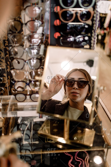 Reflection of confident woman trying sunglasses seen in mirror at fashion store