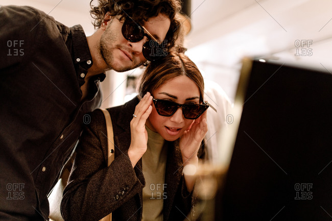 Smiling woman trying fashionable sunglasses with friend at store