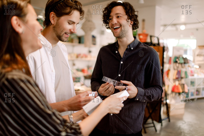Smiling male friends talking to saleswoman in store