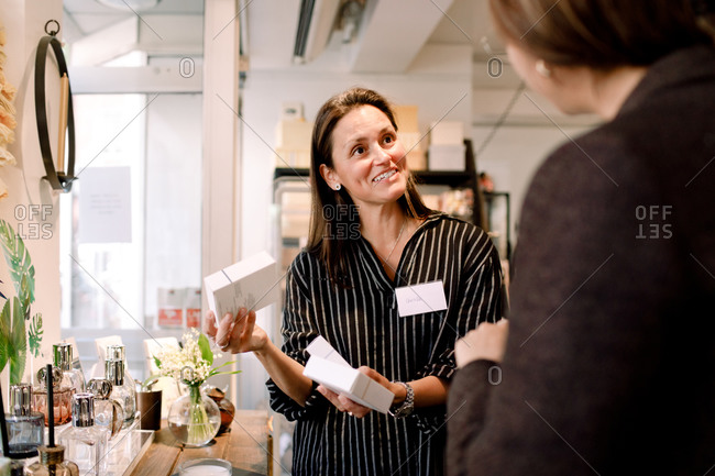Smiling saleswoman with perfume box talking to customer at store