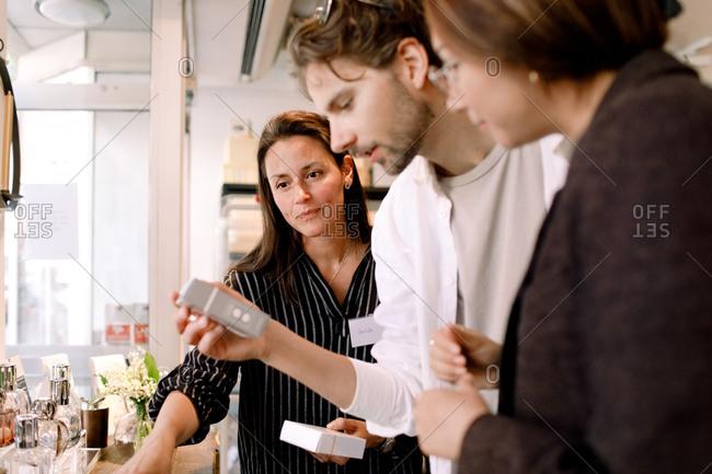 Saleswoman showing perfume box to couple at fashion store