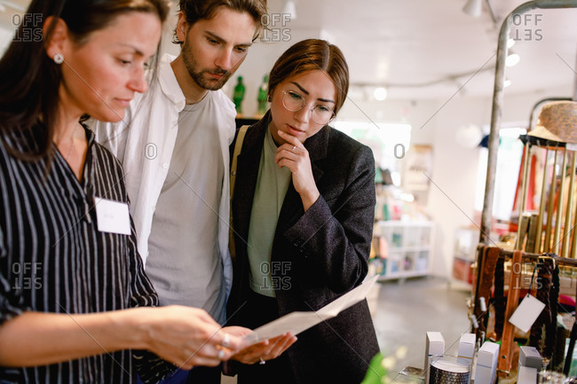 Saleswoman showing brochure to couple at fashion store
