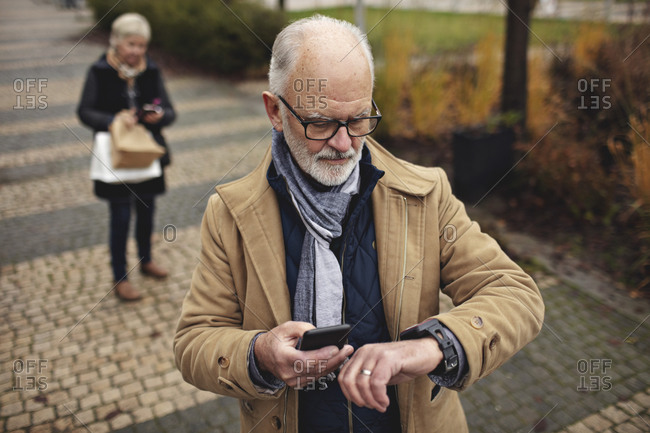 Senior man with smart phone checking the time while partner standing behind on footpath