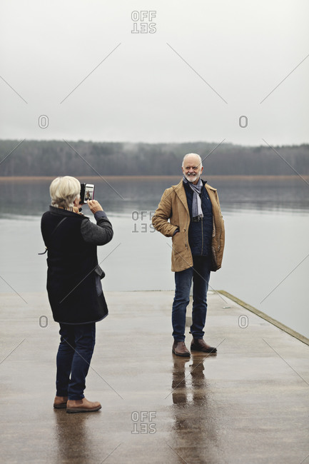 Full length of senior woman photographing male partner at lakeside against clear sky