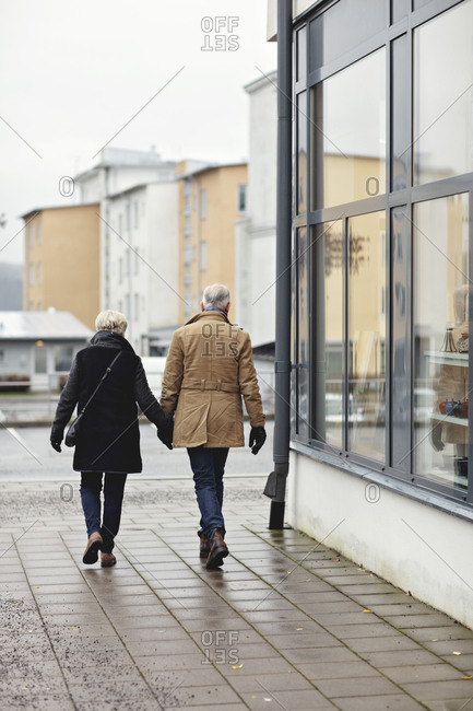 Rear view of senior couple holding hands while walking on sidewalk during winter
