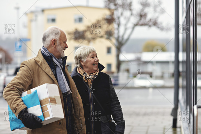 Smiling senior couple with package in city during winter