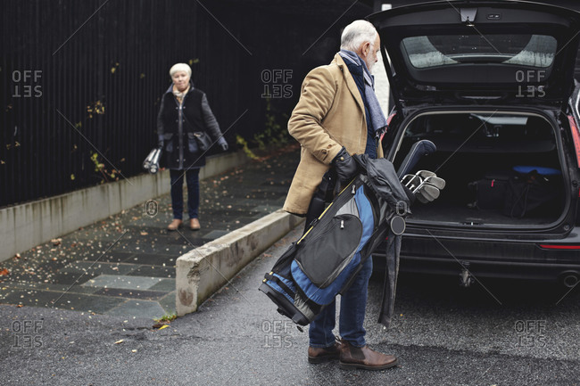 Senior man holding golf bag by car trunk while female partner standing on sidewalk during winter