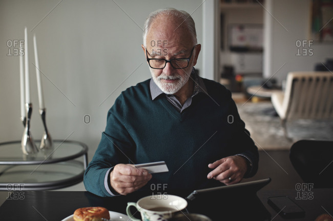 Wrinkled man holding credit card by digital tablet while sitting at dining table in living room