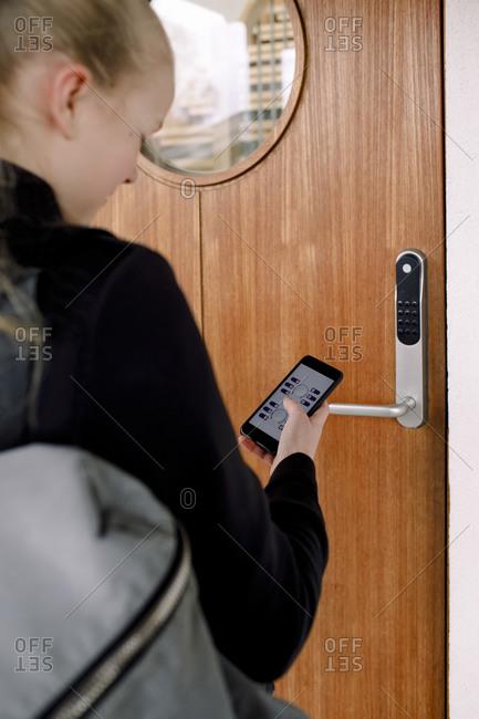 Rear view of girl with smart phone unlocking door