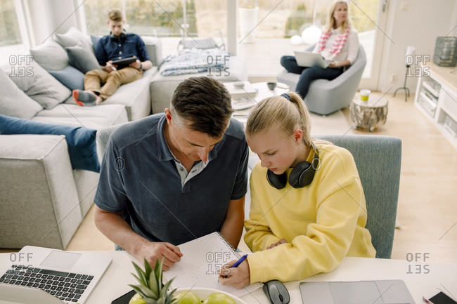 High angle view of father teaching daughter while sitting at table in living room