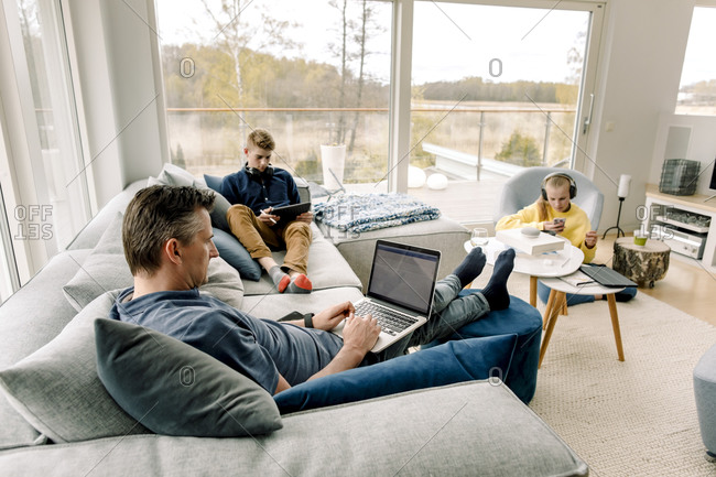 High angle view of father and children using wireless technology at home