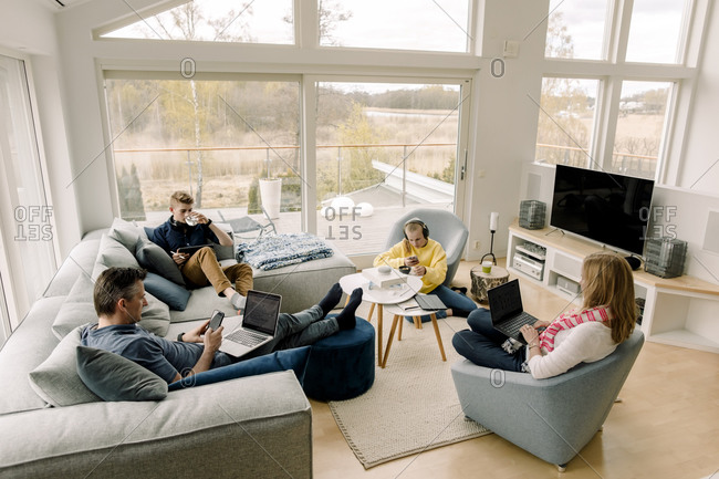 High angle view of family using technology while sitting in living room